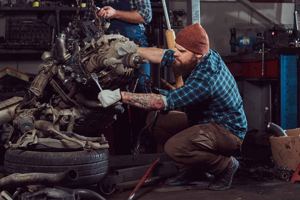 Brutal tattooed mechanic repairs the car engine in the garage. Service station.
