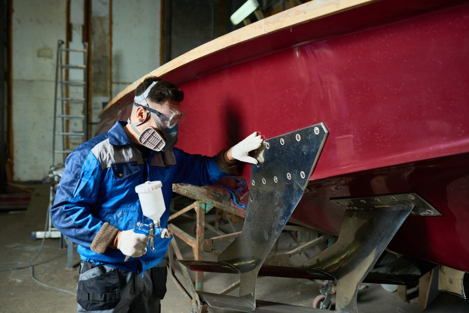 Man Painting Boats in Yacht Workshop