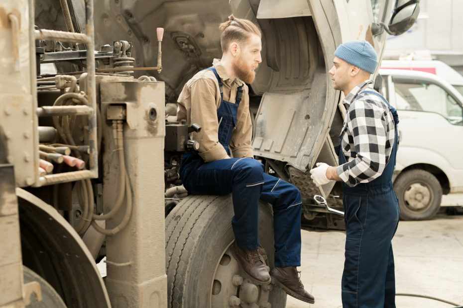 Mechanics Discussing Repair Of Truck